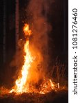 Small photo of Burning fire in the night. Hot flames and sparks rise up.