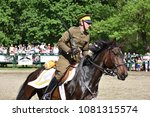 Small photo of WARSAW, POLAND - MAY 01, 2018: Polish cavalryman (uhlan) of 1930s with a sabre on a gallop. Cavalry show in Royal Lazienki park during Labor day celebration.