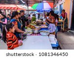 Small photo of Santiago Sacatepequez, Guatemala - November 1, 2017: Local Maya women dressed in traditional clothing sell food in the street to people visiting the giant kite festival on All Saints' Day.