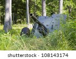 Second world war cannon hiding in high grass - stock photo