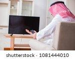 arab businessman watching tv at ... | Shutterstock . vector #1081444010