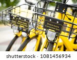 Small photo of Seattle, Washington/ USA - April 30, 2018: Close up on the handle bar basket with Share More Consume Less sign, on a yellow Ofo bike, part of an app based bicycle sharing network