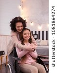 Small photo of Moms hug. Happy crippled girl using wheelchair while woman admiring her
