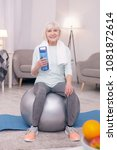 Small photo of Vital hydration. Cheerful elderly woman sitting on the balance ball and posing with a bottle of water while smiling
