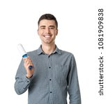 Small photo of Young man with lint roller on white background. Dry-cleaning service