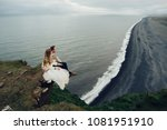 Stylish happy bride and groom hugging each other. On the background of volcanic cliffs on an amazing coast of west Iceland.