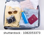 flat lay packed clothes luggage ... | Shutterstock . vector #1082053373