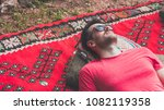 handsome hipster lying on rug... | Shutterstock . vector #1082119358