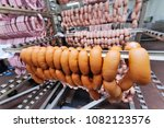 sausages hanging in a smoking... | Shutterstock . vector #1082123576