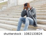 Small photo of Stressed african-american man sitting alone with headache at university on stairs. Black depressed student guy failed exams, expelled from college, copy space