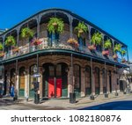 French Quarter architecture in New Orleans, Louisiana. House in French Quarter in 18th century Spanish style with cast iron galleries with hanging plants and pastel colors.