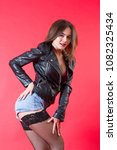 Small photo of Girl in a leather jacket and short denim shorts