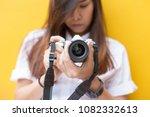 pretty woman holding camera...   Shutterstock . vector #1082332613