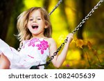 little child riding on a swing | Shutterstock . vector #1082405639