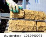 man builds a brick wall at a... | Shutterstock . vector #1082440073