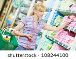 woman with basket choosing towel at household chemistry goods department of shopping mall - stock photo
