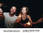 happy couple with sparklers in...   Shutterstock . vector #1082599799
