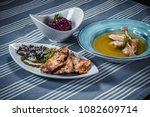 Small photo of Set of three dishes. Business lunch of three dishes. Three dishes on white plates on a table with a blue tablecloth striped. Soup, salad and hot dish.