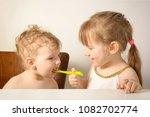 the older sister feeds the... | Shutterstock . vector #1082702774