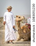 Small photo of Ibri, Oman, 28th April 2018: young omani man with his camel