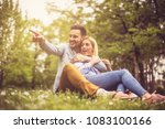 young happy couple sitting on... | Shutterstock . vector #1083100166