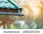 rain flows down from a roof down | Shutterstock . vector #1083225254
