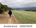 Woman Walking Through Fields Of ...