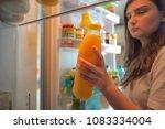 teenage girl takes the orange... | Shutterstock . vector #1083334004