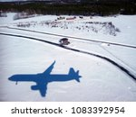 Landing in Oulu, Northern Ostrobothnia, Finland. The shadow of the plane against a snow covered field with houses and forests in the background.