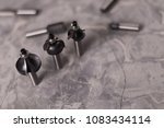 Small photo of Scattered set of steel router bit for milling cutter and row of three bits on old broken worn gray concrete floor with copy space