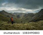 hill walker looking into valley | Shutterstock . vector #1083490883