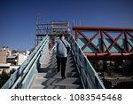 Small photo of A man passes a bridge over the closed central train station of Athens a 24-hour strike of Members of the Panhellenic Federation of Railway Workers in Athens, Greece on Sep. 14, 2107.