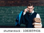 Small photo of Young professor holding pile of books looking over his glasses. Aristocrat scholar in elite college.