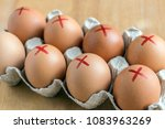 Small photo of Brown farm eggs with red cross in white carton. Eggs recall over salmonella. How to buy safest eggs after recall