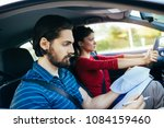 Small photo of Driving school or test. Beautiful young woman learning how to drive car together with her instructor.