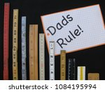 Small photo of A Father's Day greeting with folding rulers and scales in metric and inches for the handyman, wood worker or carpenter, representing concepts of measurement, metrics, precision, accuracy and results.