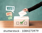 a hand placing a voting slip... | Shutterstock . vector #1084273979