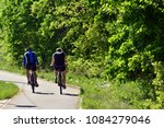 two people ride a bicycle on a... | Shutterstock . vector #1084279046