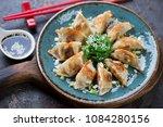 Turquoise plate with pan fried gyoza dumplings, seaweed salad and soy sauce, studio shot, selective focus