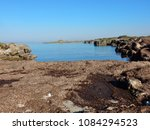 Rocks covered with seaweed of sea grass in front of the ruined Torre Castiglione, Porto Cesareo Marine Protected Natural Area