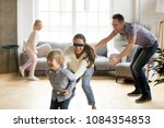 Small photo of Blindfolded mother catching little son playing hide and seek at home, happy children having fun with mom and dad, parents with kids spending time together in living room, weekend family games concept