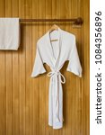 white bathrobe with towel on... | Shutterstock . vector #1084356896