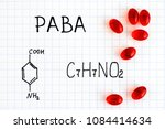 Small photo of Chemical formula of PABA with red pills. Close-up.