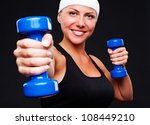 healthy young woman with blue dumbbells. studio shot over black background - stock photo