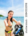 Small photo of Woman with snorkelling equipment standing in ocean, making a tempting gesture
