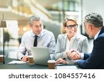 two mature businesspeople... | Shutterstock . vector #1084557416