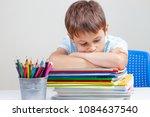 upset schoolboy sitting at desk ... | Shutterstock . vector #1084637540