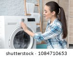 young woman doing laundry at...   Shutterstock . vector #1084710653