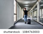 Small photo of Guy in a crimson hat with a black travel bag walks in the airport. He wears a black T-shirt, shoulder pouch, dark sneakers and blue jeans. Man looks in the window. Shoot from the back. Horizontal.