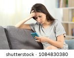 sad teen reading bad news in a... | Shutterstock . vector #1084830380